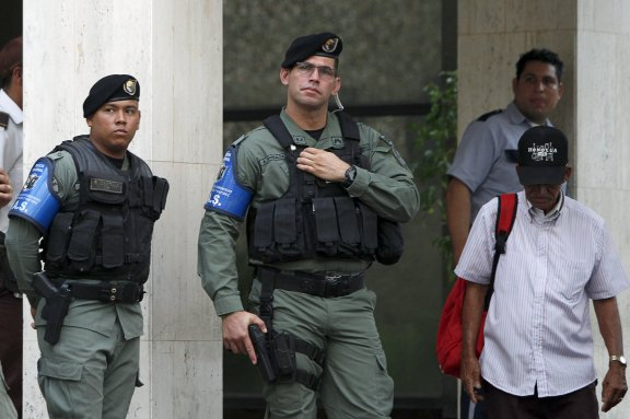 Police officers stand guard at the entrance of the Mossack Fonseca law firm office in Panama City